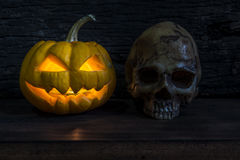 Halloween pumpkin head jack lantern with human skull. Halloween pumpkin head jack lantern with scary evil faces and human skull over wooden background in stock image
