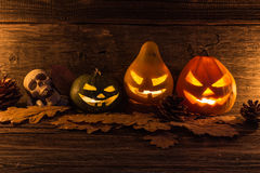 Halloween pumpkin head jack lantern with scary evil faces. Dark wooden background. Skull stock photos