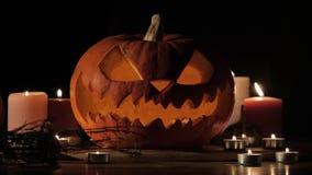 Halloween pumpkin head Jack-o-lantern with burning candles over black background. Halloween holidays art design, celebration. Halloween holiday night scene. 4K stock footage