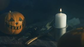 Halloween pumpkin head lantern with burning candles on a black background on wooden table with knife and spoon stock footage
