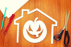 Halloween pumpkin into home cut out of paper lying on a table Stock Photos