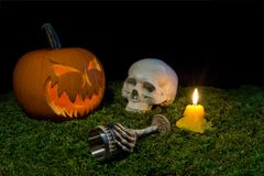 Halloween pumpkin, human skull, goblet and candles glowing in th stock photo