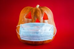 Free Halloween Pumpkin In A Protective Medical Mask On A Red Background Stock Images - 192473874