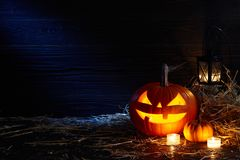 Halloween pumpkin jack lantern in dark barn, holiday concept stock photography