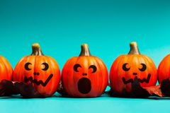 Halloween pumpkin jack o lantern decor with funny faces. Halloween holiday background. Halloween pumpkin jack o lantern decor with funny faces on blue royalty free stock photo