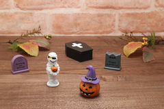 Halloween pumpkin Jack O' lantern, graves, mummy, autumn leaves and coffin on wood. Royalty Free Stock Photos