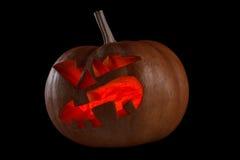Halloween pumpkin Jack O Lantern shiny inside on black Royalty Free Stock Images