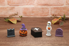 Halloween pumpkin Jack O' lantern, graves, mummy, autumn leaves and coffin on wood. Royalty Free Stock Photography
