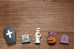 Halloween pumpkin Jack O' lantern, graves, mummy, and coffin on wood. Royalty Free Stock Photo