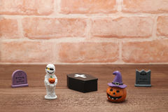 Halloween pumpkin Jack O' lantern, graves, mummy, and coffin on wood. Stock Images