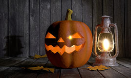 Halloween pumpkin and kerosene lantern in a wooden barn Royalty Free Stock Photos