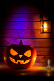 Halloween pumpkin with a lantern and a candle on wooden backgrou Stock Photos