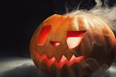 Halloween pumpkin lantern with dry leaves with burning eyes royalty free stock images