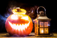 Halloween pumpkin with lantern and smoke. Halloween pumpkin with lantern and mystic smoke at wooden old table Stock Images