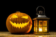 Halloween pumpkin with lantern on wooden old table. Halloween pumpkin with lantern and candle light at old wooden table with black background Stock Image