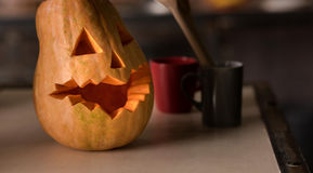 Halloween pumpkin lying on the table in the kitchen. Halloween coming soon. Halloween Jack o lantern lying on the table in the kitchen Stock Photography