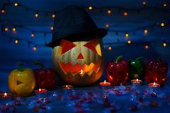Halloween pumpkin in mystical shadow, peppers with curved faces, candies, bokeh effect lights, window sill royalty free stock photos
