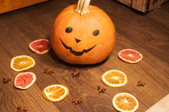 Halloween pumpkin, near dried fruits. On wooden ground Stock Images