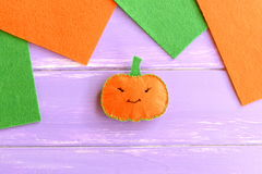 Halloween pumpkin ornament, orange and green felt pieces on wooden background with blank place for text. Royalty Free Stock Images