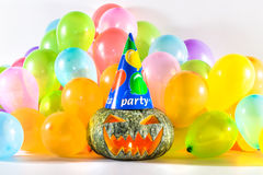 Halloween Party. Halloween Pumpkin Party. A pumpkin head with hat, celebrating halloween with colorful balloons. Isolated, white background Royalty Free Stock Image