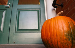 Halloween Pumpkin. Pumpkin placed in front of green door waiting for Halloween to be carved Royalty Free Stock Photography