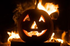 Halloween pumpkin with scary face on fire background. stock photos