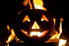 Halloween pumpkin with scary face on fire background. royalty free stock photo