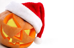 Halloween pumpkin shiny inside wearing christmas hat on white ba Stock Image