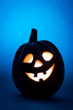 Halloween pumpkin, silhouette of funny face on blue background. Royalty Free Stock Image