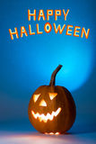 Halloween pumpkin, silhouette of funny face on blue background. Royalty Free Stock Images