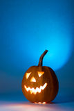 Halloween pumpkin, silhouette of funny face on blue background. Stock Image