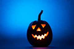 Halloween pumpkin, silhouette of funny face on blue background. Royalty Free Stock Photos