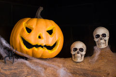 Halloween pumpkin and skull in a fireplace Stock Images