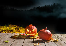Halloween pumpkin smiling in the night. Carved Halloween pumpkin smiling in the night next to leaves. Pumpkin before misty night sky. Pumpkin on the wooden deck Stock Images