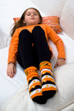 Halloween Pumpkin Socks Girl Sofa. A young girl in an orange shirt lies on a white sofa with her Halloween socks with pumpkin motifs in focus in the foreground royalty free stock photography