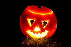 Halloween pumpkin on some grass. Halloween pumpkin lit by a candle on some grass Royalty Free Stock Photo