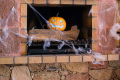 Halloween pumpkin and spider web in a fireplace Royalty Free Stock Photo