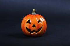 Halloween pumpkin standing on dark background Royalty Free Stock Photos
