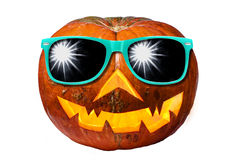 Halloween pumpkin with sunglasses isolated. Halloween pumpkin Jack O Lantern wearing sunglasses and shiny inside isolated Royalty Free Stock Photos