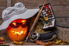 Halloween pumpkin with wading boots and fly-fishing Royalty Free Stock Photo