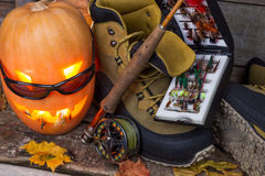Halloween pumpkin with wading boots and fly-fishing Stock Images