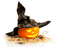 Halloween Pumpkin With Witches Hat. Halloween jack o lantern carved pumpkin wearing witches hat on straw with spiders and white background Stock Image