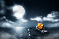 Halloween pumpkin in wooden boat on foggy lake stock images