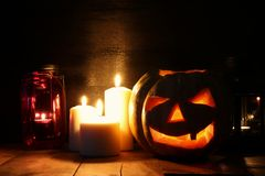 Halloween Pumpkin on wooden table in front of spooky dark background. Jack o lantern Royalty Free Stock Images