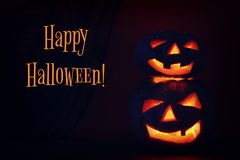 Halloween Pumpkin on wooden table in front of spooky dark background. Jack o lantern Stock Images