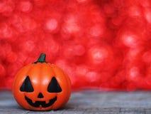 Halloween pumpkin on wooden table over red bokeh backgroun Stock Photo