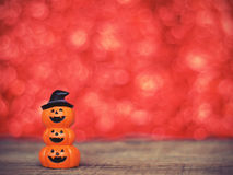 Halloween pumpkin on wooden table over red bokeh backgroun Royalty Free Stock Photography