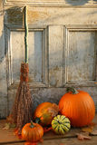 Halloween pumpkins. Pumpkins, broom and gourds at the door ready for halloween royalty free stock photo