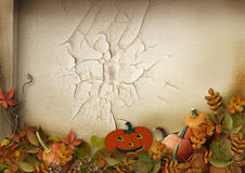 Halloween pumpkins and autumn leaves on cracks background royalty free stock image