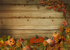 Halloween pumpkins and autumn leaves on wooden background Stock Photo